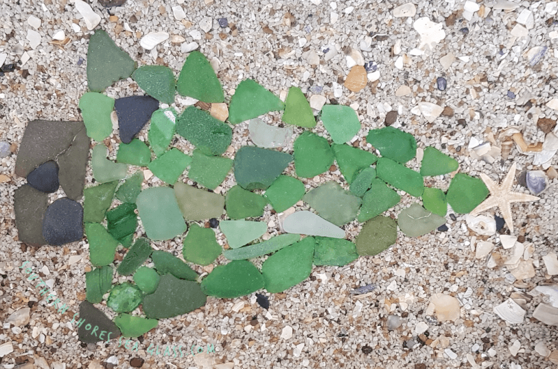 Close up of sea glass Christmas tree mosaic on sand