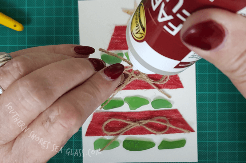 gluing the rustic twine ribbon to the Christmas tree card